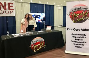 2 LaFontaine employees at Job Fair behind LaFontaine desk